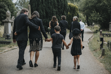 Grieving family walking through a cemetery Banco de Imagens - 112594702