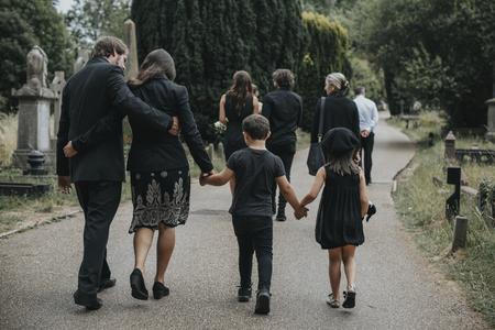 Trauernde Familie, die durch einen Friedhof geht