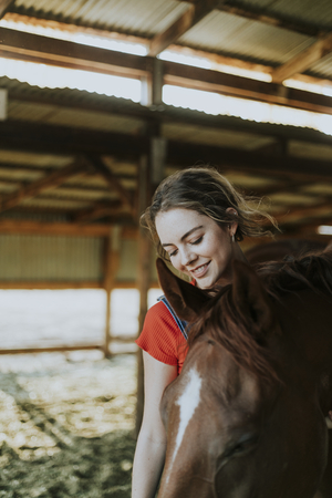 Girl grooming a chestnut horse
