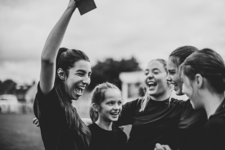 Cheerful female football players celebrating their victory