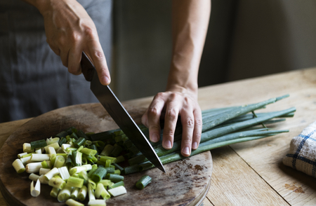 Cook chopping spring onions on a cutting board