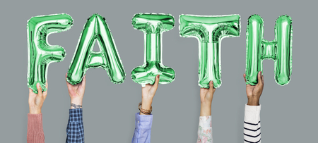 Hands holding faith word in balloon letters Archivio Fotografico