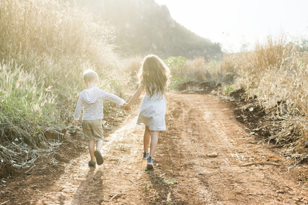 Brother and sister running together at a farm