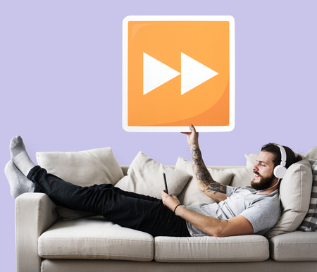 Male on a couch holding a fast forward button