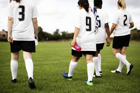 Junior female football players walking on a field Stock Photo