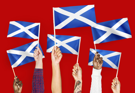 Hands waving flags of Scotland Stock Photo
