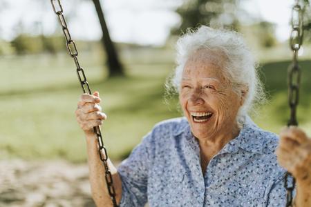 Fröhliche ältere Frau auf einer Schaukel auf einem Spielplatz