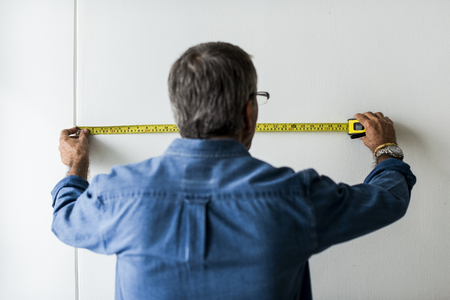 Man measuring the wall with a measuring tape 版權商用圖片