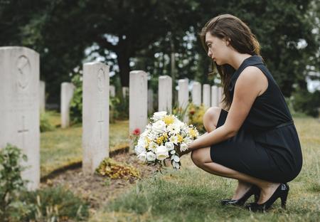 Jonge weduwe legt bloemen bij het graf Stockfoto