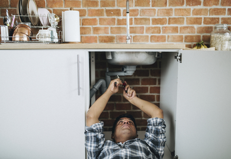 Plumber lying on the floor fixing a kitchen sink Banque d'images - 112595166