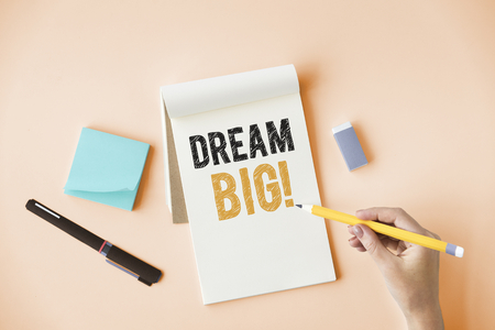 Hand writing Dream big on a notepad