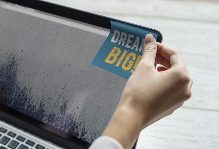 Dream big phrase written on a sticky note
