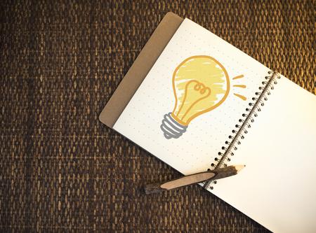 Light bulb drawn on a notebook Stock Photo