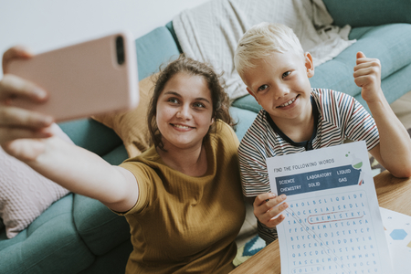 Sister taking a selfie with her little brother Stock Photo