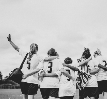 Female football players huddling and walking together Stock Photo