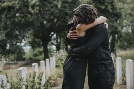 Marido tratando de consolar a su esposa en un cementerio