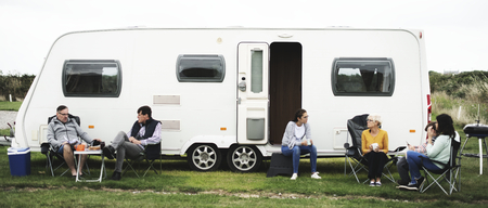 Group of people sitting outside a trailer park
