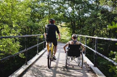 Couple sur un exercice ensemble sur un vélo et en fauteuil roulant