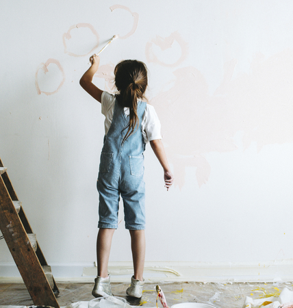 Young girl painting the walls pink