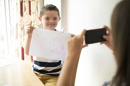 Little boy showing off his drawing