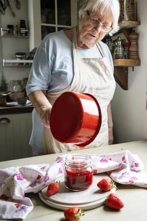 Old woman making homemade jam