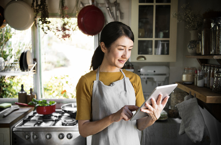Happy woman reading a recipe from a screen Stock Photo