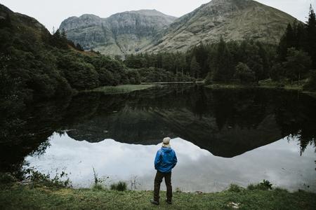 Uomo in piedi in riva al fiume nelle Highlands Archivio Fotografico
