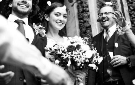 Family throwing rose petals at the newly wed bride and groom Stock Photo