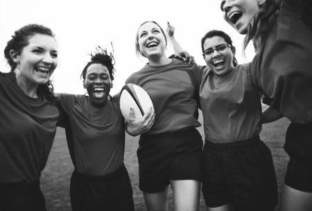 Energetic female rugby players celebrating