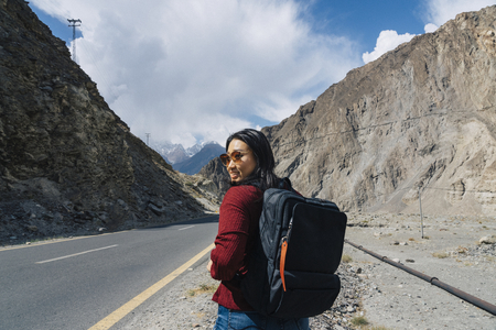 Female backpacker walking on a mountainous highway
