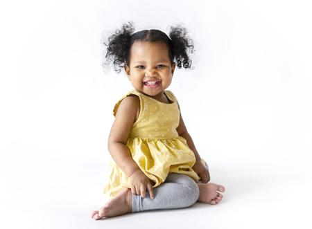 Heureuse petite fille vêtue d'une robe jaune assise