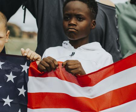 Grupo de niños diversos que muestran una bandera estadounidense en una protesta