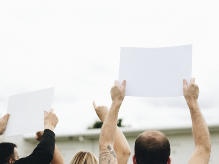 Rear view of activists showing papers while protesting Stock Photo