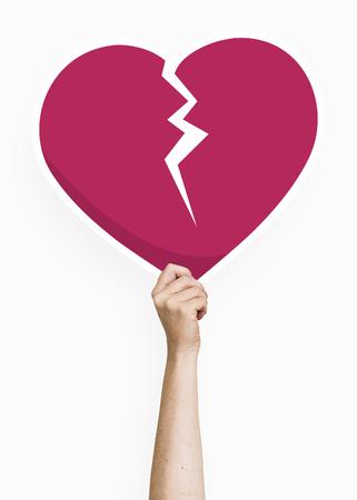 Hand holding a broken heart cardboard prop