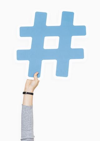 Hand raised holding hashtag icon Stock Photo