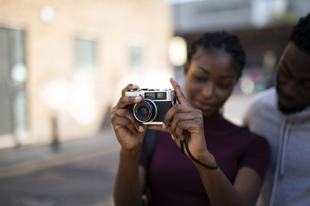 Woman using an analog film camera Foto de archivo