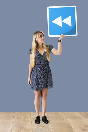 Woman holding a rewind icon in a studio Stock Photo - 112893033