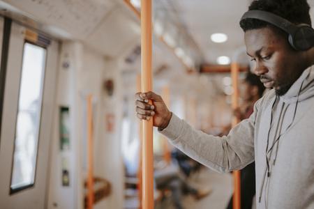Standing passenger listening to music on the train 免版税图像 - 112893037
