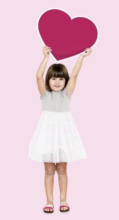 Happy girl holding a heart icon Stock Photo