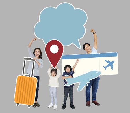 Joyeuse famille tenant des icônes de voyage et un billet Banque d'images