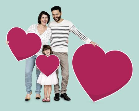 Famiglia felice che tiene icone a forma di cuore heart