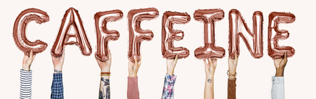 Hands holding caffeine word in balloon letters Stock Photo