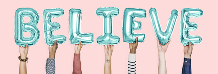 Hands holding believe word in balloon letters