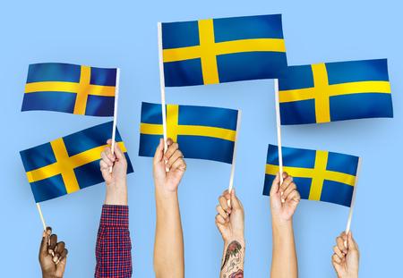 Hands waving the flags of Sweden Stockfoto