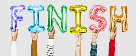 Hands holding finish word in balloon letters Stockfoto