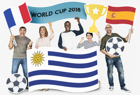 Diverse football fans holding the flags of France, Uruguay and Spain Фото со стока