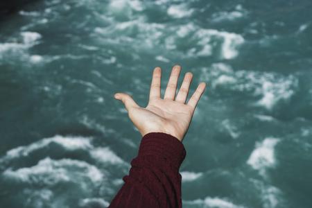 Mano femenina con vistas al agua azul