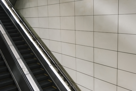 Escalator with blank tiled wall Imagens