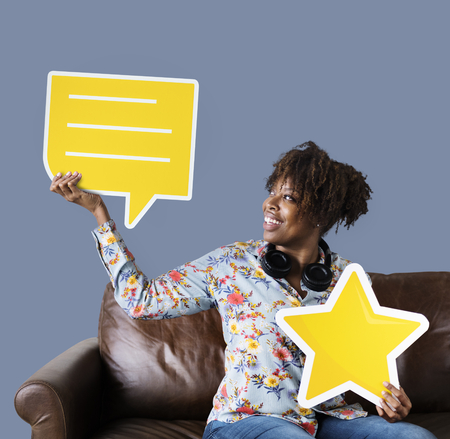 Cheerful woman holding a speech bubble and star icon Stock Photo