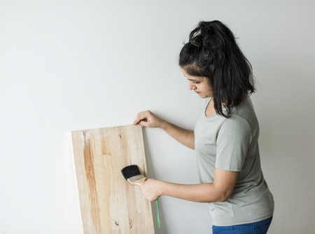 Woman coating a wooden plank with lacquer
